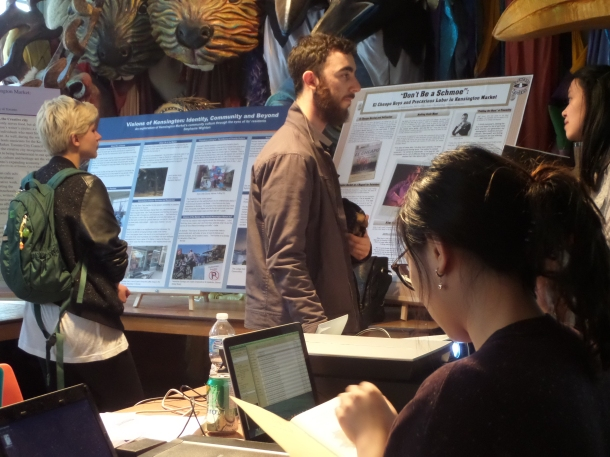 Residents and visitors stop in to read about student research on the market.