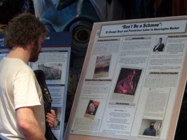 A Kensington Market resident reads a poster in which he is featured.
